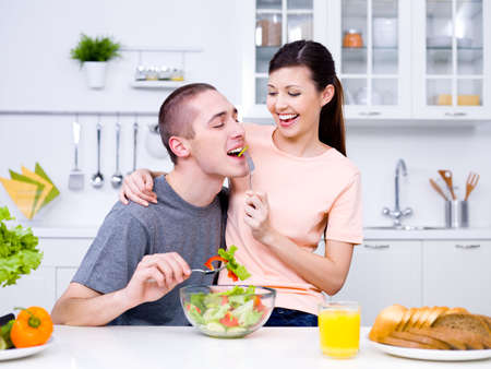 vegetables young couple: Happy playful young couple eating together in the kitchen Stock Photo