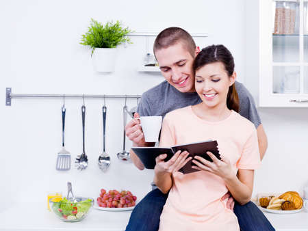 Beautiful young loving couple reading the cookbook together in the kitchen photo