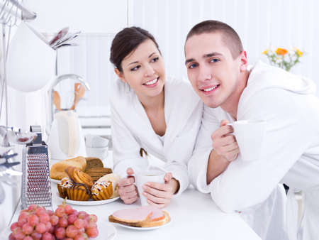 Happy loving young couple having breakfast together in the kitchen photo