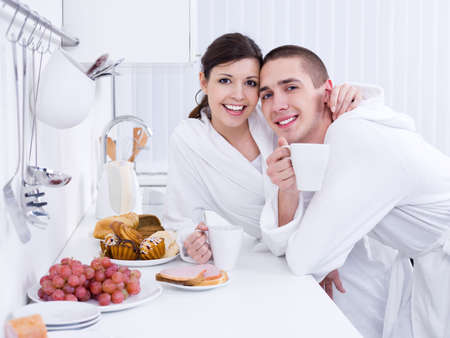 Portrait of happy young loving couple having breakfast together photo