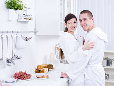 Young beautiful smiling couple embracing in the kitchen photo