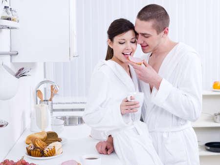 Beautiful happy loving couple having breakfast in the kitchen photo