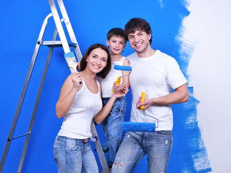 幸せな家族改修 - 屋内を行ってペイント ブラシに笑みを浮かべて