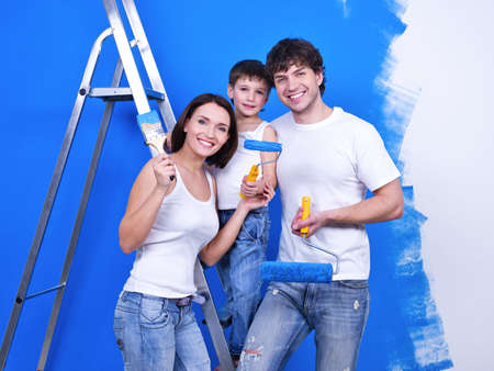 Happy smiling family with paintbrushes doing renovation - indoors photo