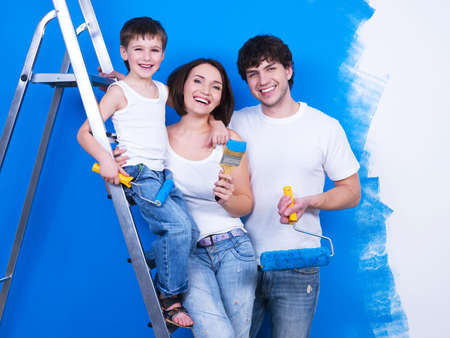 Portrait of happy young family standing together with paintbrush and stepladder photo