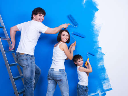 brush painting: Happy young family with little son painting the wall