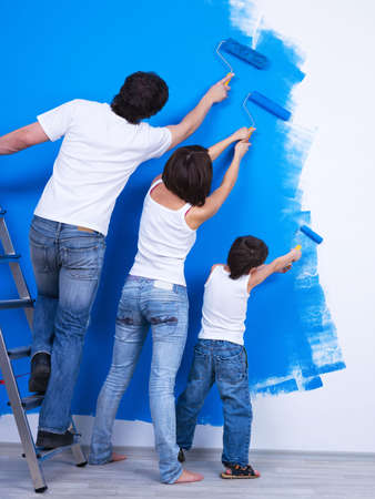 home improvements: Young family brushing the wall together into the blue color