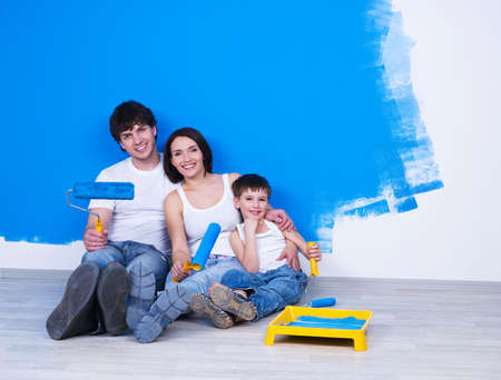 Portrait of happy friendly family sitting on the floor with paintbrush photo