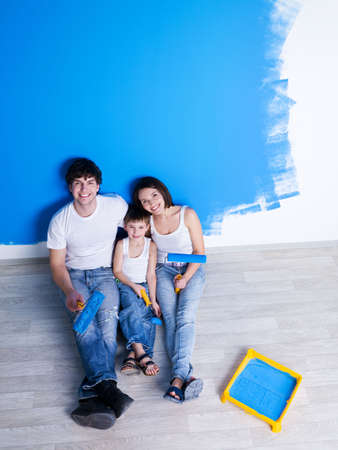 home renovations: Happy family having a rest after painting the wall - high angle Stock Photo