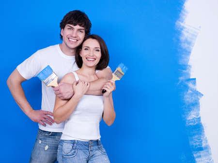 coppia in casa: Ritratto di felice coppia giovane sorridente con paitbrushes  Archivio Fotografico