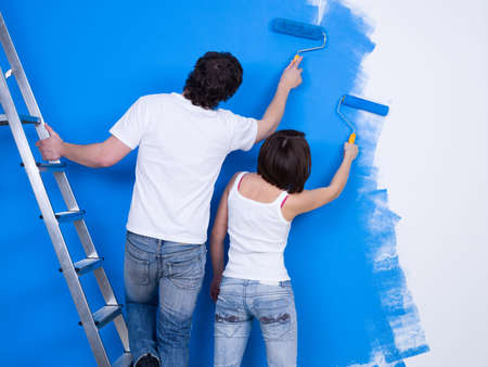 synchronously: Young couple painting the wall with roller together
