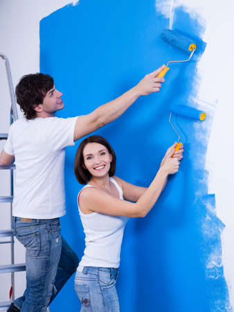 Happy cheerful couple with rollers painting the wall - indoors photo