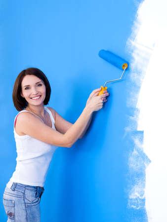 Mooie jonge gelukkige vrouw borstelen de muur - verticaal