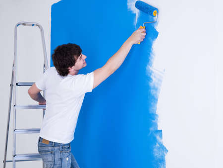 adult wall: Handsome young man painting the wall in blue - horizontal