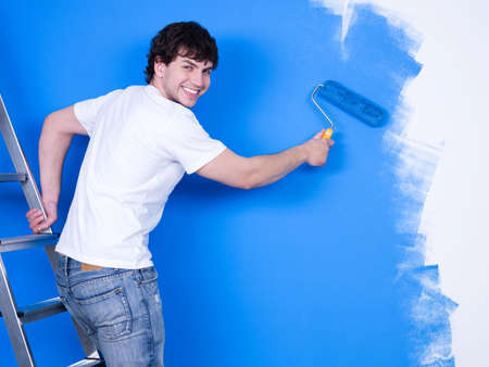 blue walls: Handsome young man with happy smile painting the wall
