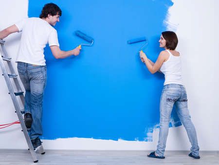 home improvement: Young couple in casuals ñoloring the wall in blue - rear view Stock Photo