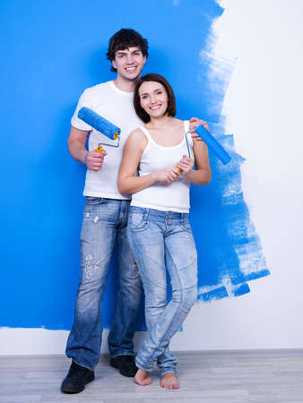 Portrait of happy young loving couple with paintbrushes near the painted wall photo