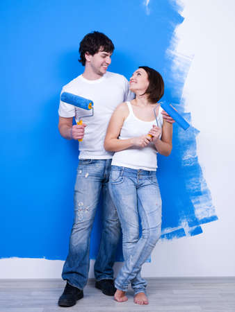 Portrait of happy loving cheerful couple near the painted wall photo