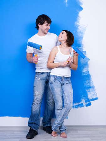 painting wall: Retrato de la feliz pareja alegre amorosa cerca de la pared pintada