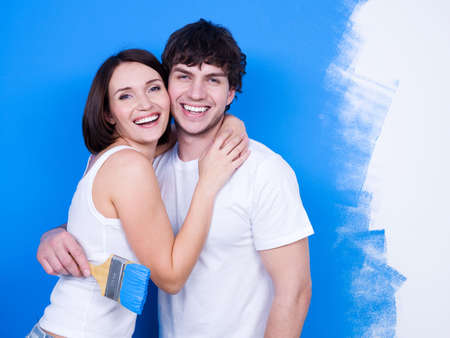 loving couples: Portrait of happy loving embracing couple at painted wall as background