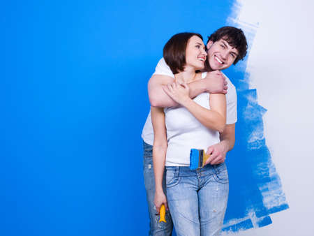 home improvements: Joyful happy embracing loving couple standing near the painted wall