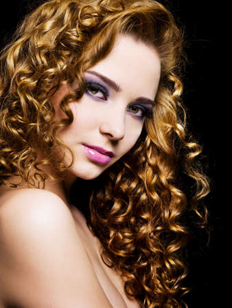 curly hair model: Portrait of a pretty adult girl with  long  hairs - On a black background Stock Photo
