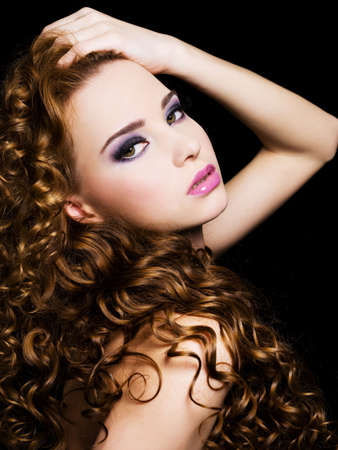 curly hair model: Bbeautiful  woman with beauty  long  hairs and bright pink make-up. On a black background