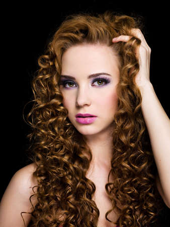 ringlet: Portrait of a beautiful  woman with  long curly hairs - On a black background Stock Photo