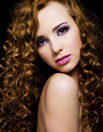 Portrait of a beautiful  woman with  long curly hairs - isolated on black background Stock Photo - 6870051
