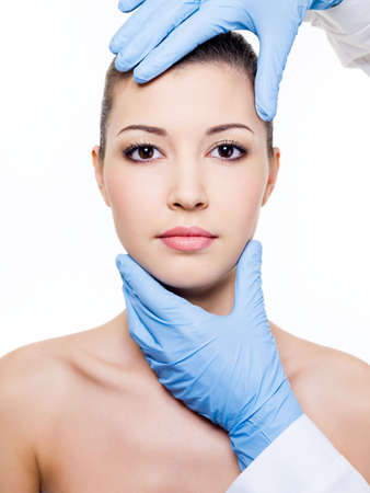 plastic glove: Plastic  surgery touching the beautiful woman face.  Isolated on white