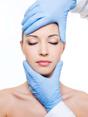 Plastic surgery touching the head of a beautiful female face with closed eyes photo