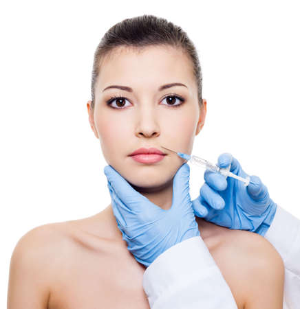Facial care.  Injection of botox in beautiful womans face - isolated white photo