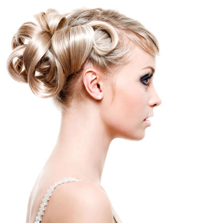 Profile of beautiful young woman with fashion hairstyle - on white background photo