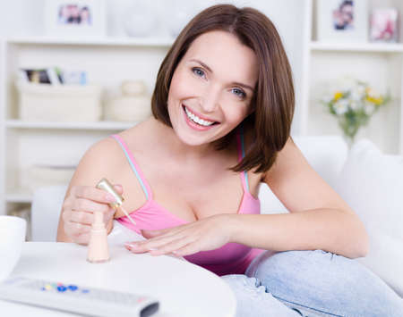manicure: Portrait of happy young cheerful beautiful woman colouring her nails Stock Photo