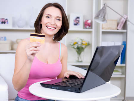 Portrait of happy young beautiful woman holding credit card and using laptop photo