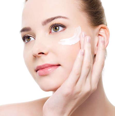 gezichtsbehandeling: Caucasian jonge vrouw schoonheid cosmetische onder ogen toe te passen.  Stockfoto