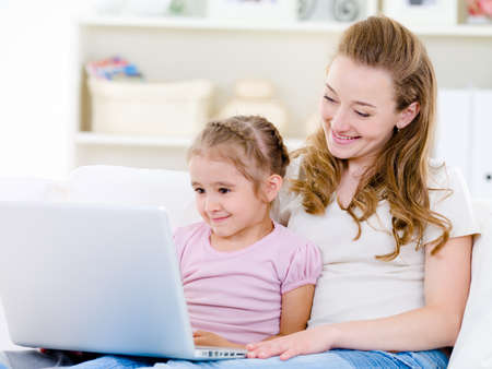 blonde mom: Young mother with little daughter sitting together at home and looking at laptop  Stock Photo