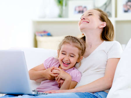 Laughing happy young mother and little daughter with laptop on the sofa at home photo