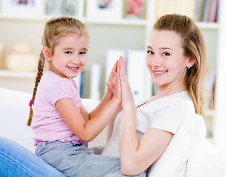Portrait of beautiful mother and dughter with happy smile  - indoors photo