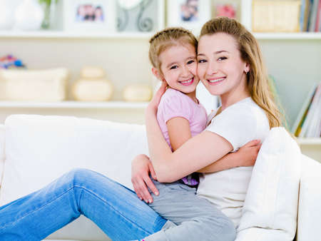 Happiness of mother with little daughter sitting together in embrase on the sofa - indoors photo