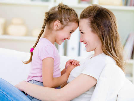 Portrait of happy smiling mother with her little daughter at home - indoors photo