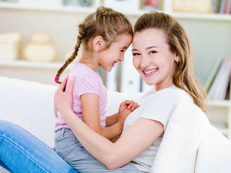 Portrait of happy smiling young woman with her little pretty daughter  -  indoors photo