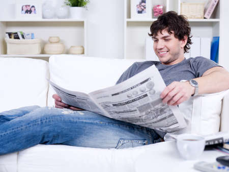 Happy smiling handsome man reading newspaper at home photo