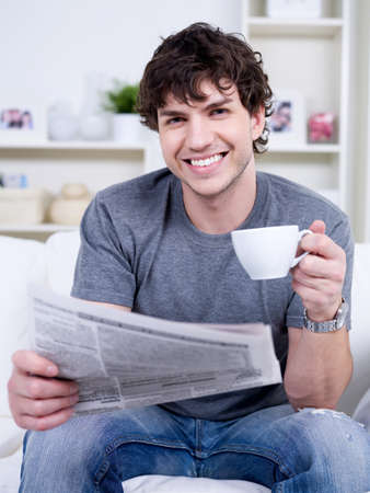 news room: Portrait of young handsome man with with cup of coffee reading newspaper Stock Photo