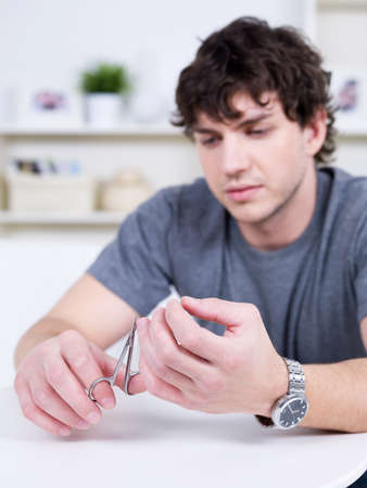 nail scissors: Portrait of handsome young candid man cutting nails - indoors Stock Photo