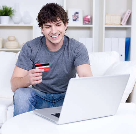 Handsome man holding credit card and using laptop for online shopping - indoors photo