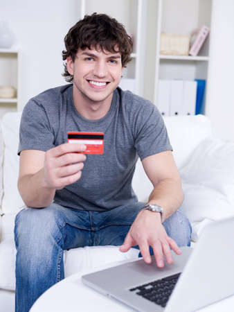 house of cards: Handsome happy smiling guy holding credit card and using laptop - indoors