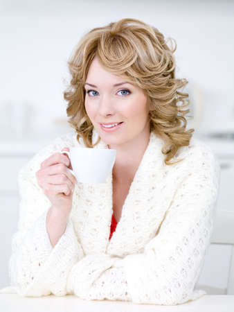 Cup of coffee for young beautiful blond woman sitting in the kitchen photo