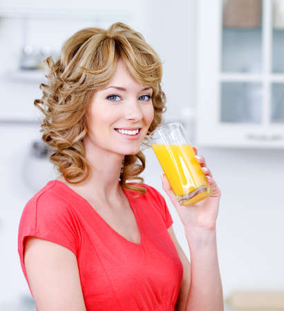 Portrait of happy smiling blonde woman drinking fresh orange juice in the kitchen photo