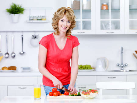 Beautiful woman preparing healthy food in the kitchen - indoors photo